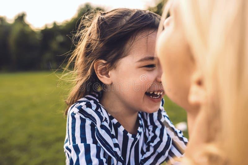 Primer tirado de la hija hermosa feliz de la niña que abraza a su madre en el parque Madre sonriente de amor e hija de risa fotos de archivo