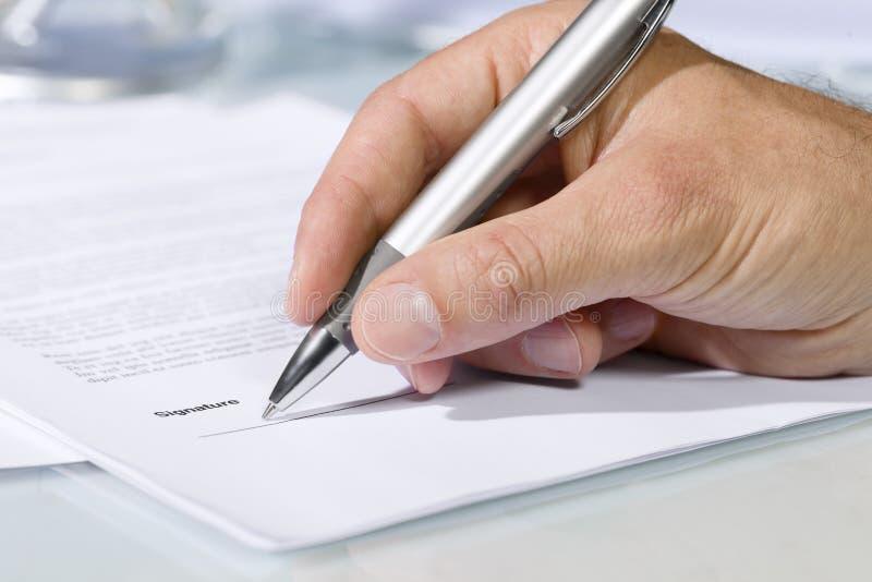Primer tirado de la mano que firma un documento imagen de archivo libre de regalías