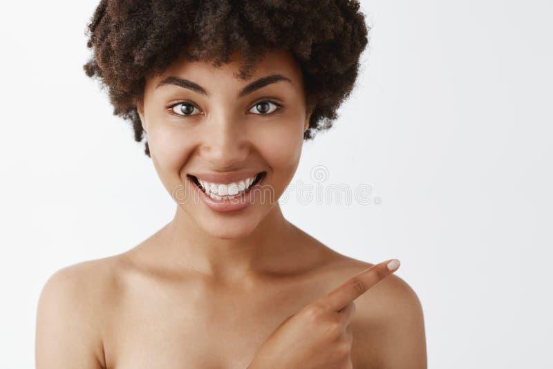 Primer tirado de la mujer de piel morena desnuda atractiva y hermosa femenina con el peinado rizado que señala en la derecha supe imágenes de archivo libres de regalías