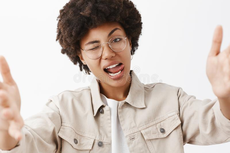 Primer tirado de lesbiana afroamericana rebelde y fresca confiada en vidrios y camisa beige, mostrando la lengua coqueta y fotos de archivo