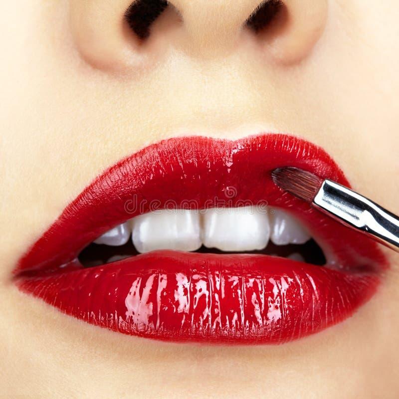 Primer tirado de maquillaje de los labios de la mujer fotografía de archivo