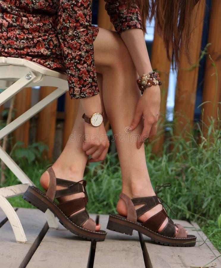 Primer tirado de pies elegantes de una hembra que lleva un vestido en el verano foto de archivo