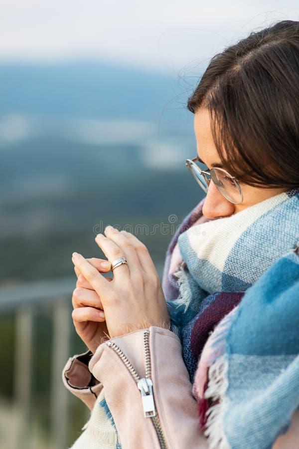 Primer tirado de una mujer hermosa con la bufanda que muestra su anillo de compromiso fotografía de archivo