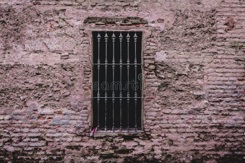 Primer tirado de una pared de ladrillo resistida vieja con una cubierta de ventana claveteada del metal él foto de archivo libre de regalías