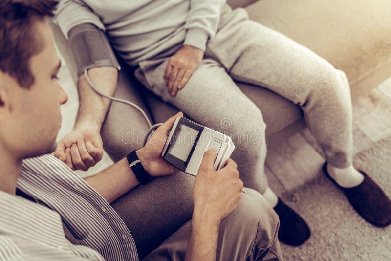 Primer tirado de varón adulto usando un metro de la presión arterial fotos de archivo libres de regalías