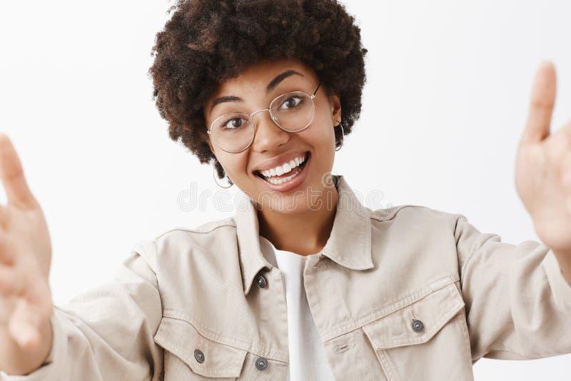 Primer tirado del afroamericano emotivo y lindo amistoso femenino en vidrios transparentes y la camisa que tiran de las manos imagen de archivo libre de regalías