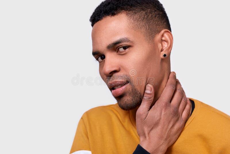 Primer tirado del hombre afroamericano joven que toca su cara y cuello con la mano y que mira a la cámara fotos de archivo libres de regalías