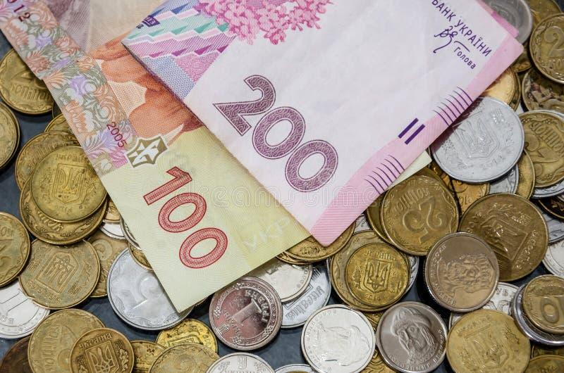 Primer ucraniano del dinero 100 y 200 billetes de banco y monedas del hryvnia Visi?n desde arriba foto de archivo libre de regalías