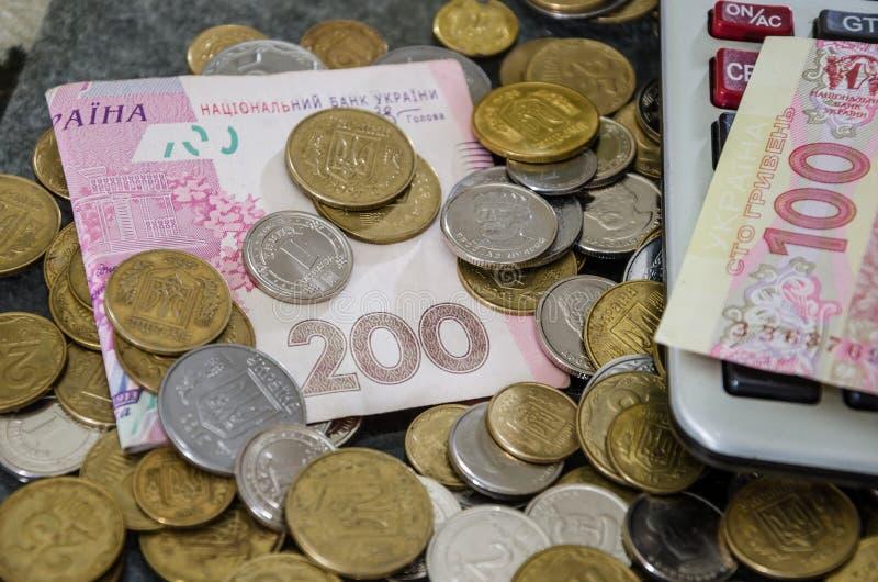 Primer ucraniano del dinero y de la calculadora 100 y 200 billetes de banco y monedas del hryvnia Visi?n desde arriba fotografía de archivo libre de regalías