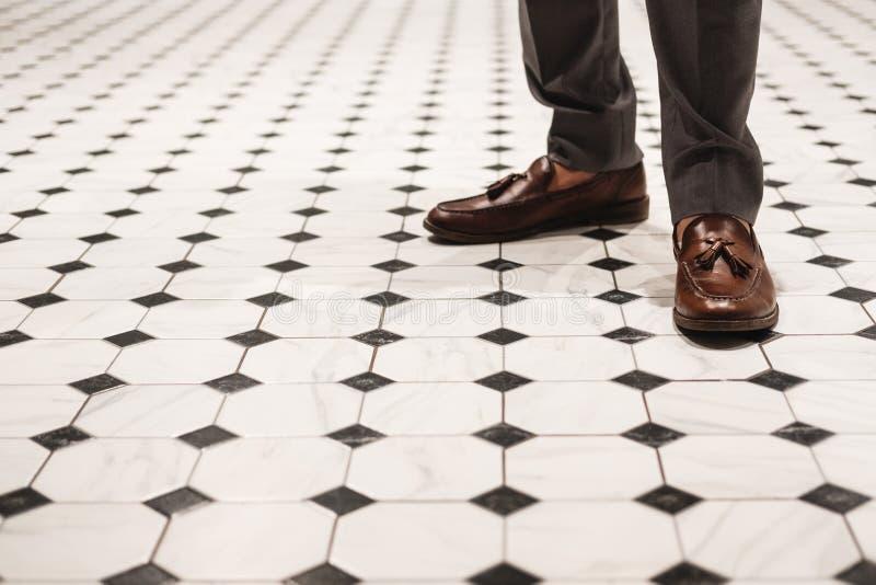 Primer un hombre que lleva los zapatos de cuero marrones, estilo clásico en piso del vintage fotografía de archivo
