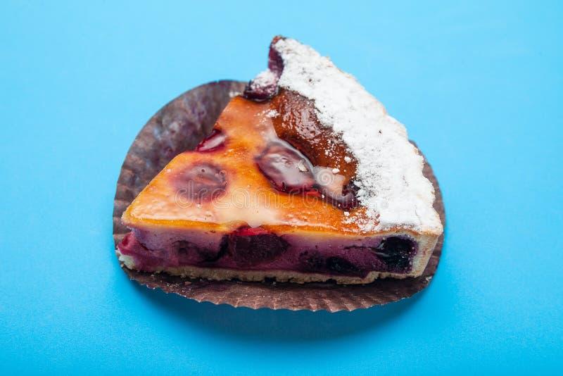 Primer, un pedazo de primer de la empanada de la cereza en un fondo azul fotografía de archivo libre de regalías