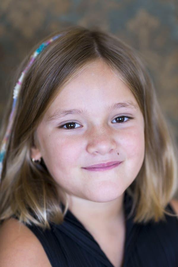 Primer vertical de la niña hermosa en negro con el pelo meneado hasta el hombro imagenes de archivo
