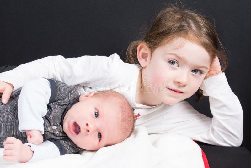 Primer y segundo niño junto en la pequeña hermana de la familia que abraza a su bebé recién nacido imagenes de archivo