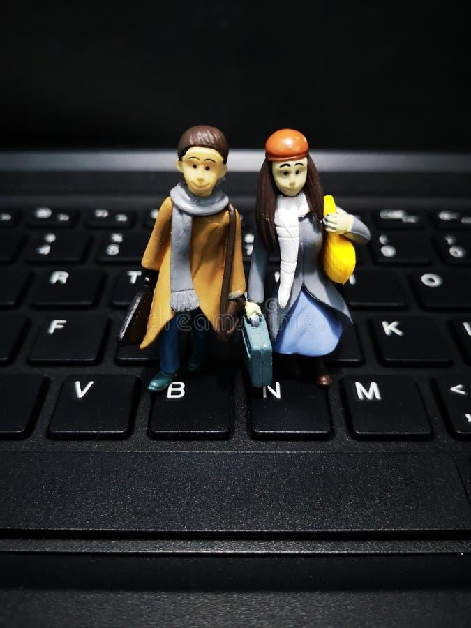 Primer y tiro macro de trabajadores miniatura con su maleta y un fondo del ordenador imágenes de archivo libres de regalías