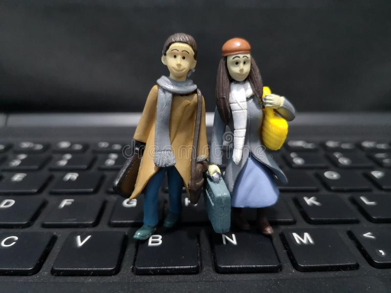 Primer y tiro macro de trabajadores miniatura con su maleta y un fondo del ordenador foto de archivo libre de regalías