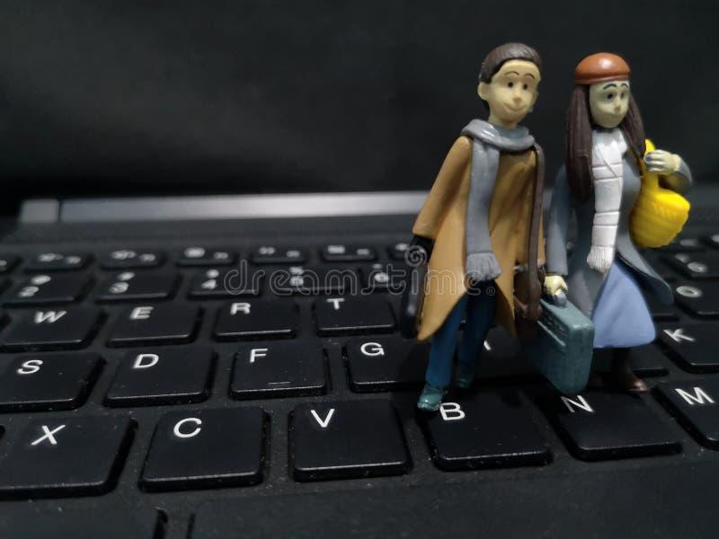 Primer y tiro macro de trabajadores miniatura con su maleta y un fondo del ordenador foto de archivo
