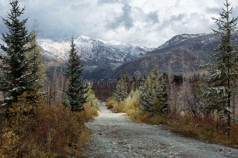 Primera nieve del otoño y camino rural en montañas fotos de archivo
