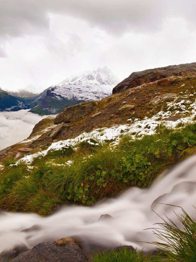 Primera nieve en el prado alpino, cascada en corriente Picos de las montañas de las montañas en fondo El agua espumosa está corri fotografía de archivo libre de regalías