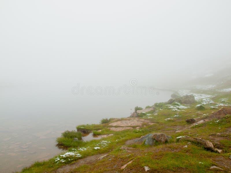 Primera nieve en montañas Lago autumn en las montañas con el nivel del espejo Picos agudos brumosos de altas montañas fotografía de archivo libre de regalías