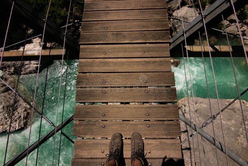 Primera opinión de la persona sobre pies en el puente suspendido por encima de la superficie en Francia imagenes de archivo