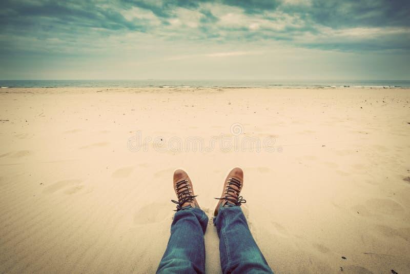Primera perspectiva de la persona de las piernas del hombre en vaqueros en la playa del otoño fotografía de archivo