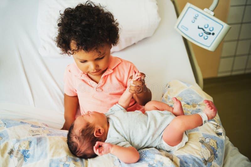 Primera reunión del niño pequeño africano adorable y de su hermano recién nacido fotos de archivo libres de regalías