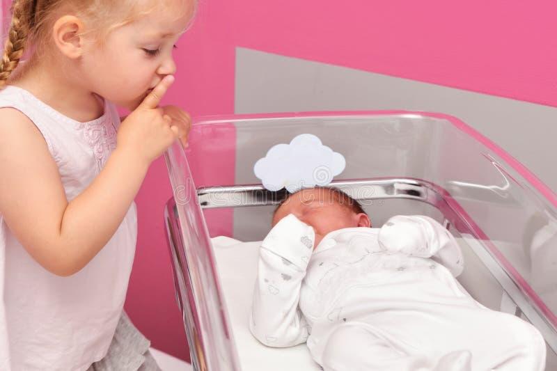 Primera reunión entre una hermana y un bebé recién nacido en la sala de hospital fotos de archivo