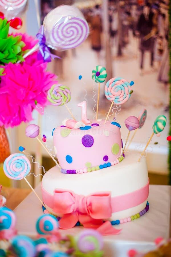 Primera torta del rosa del cumpleaños con los lollypops y una vela para poco bebé y decoraciones para el partido imagenes de archivo