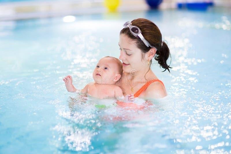 Primera vez del pequeño bebé en una piscina imagen de archivo