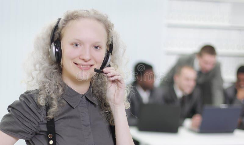 Primero plano un empleado de mujer joven de un centro de atención telefónica foto de archivo