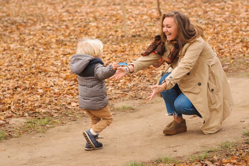 Primeros pasos de progresi?n Funcionamiento lindo del niño pequeño a su madre en el parque del otoño Mamá feliz y niño que juegan imagen de archivo
