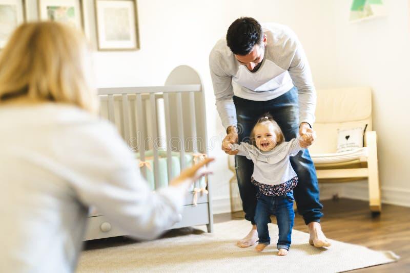 Primeros pasos del pequeño bebé con la ayuda del padre fotografía de archivo libre de regalías