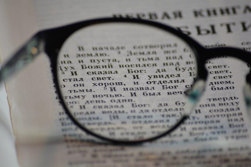 Primeros versos de la génesis a través de los vidrios de lectura fotos de archivo libres de regalías
