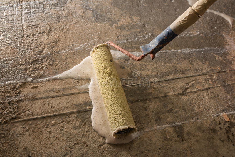 Priming concrete floor. Before laying tiles on it, the final preparatory stage for strengthening the surface royalty free stock image