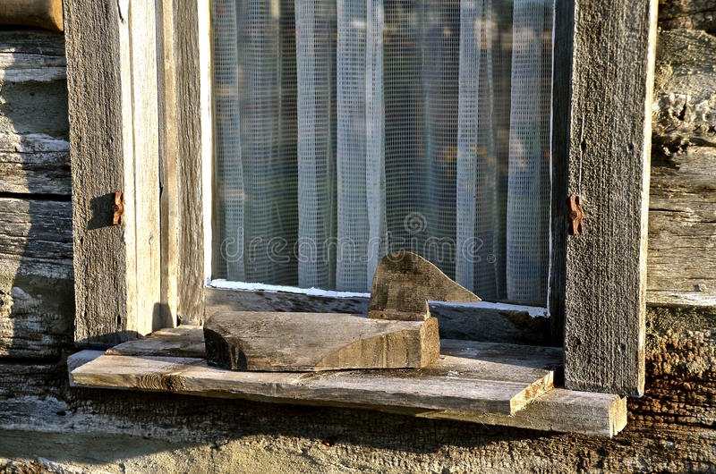 Primitive duck on window ledge. A primitive carved wood duck rests on a log cabin window ledge royalty free stock photo