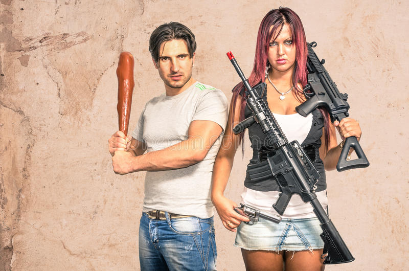 Primitive man and modern woman with weapons - Funny Couple. Primitive men and modern women with weapons stock photos