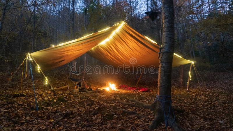 Primitive Tarp Shelter with campfire and fairy lights. Survival Bushcraft setup in the Blue Ridge Mountains near Asheville. During stock images