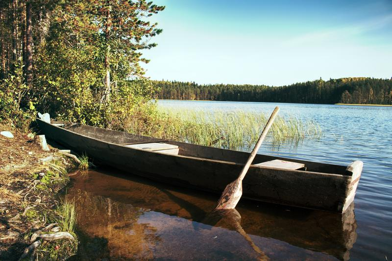 Primitive wooden boat of the Northern peoples. Primitive wooden boat of Northern peoples (Veps region) with one oar for alternate rowing from right side and on stock image