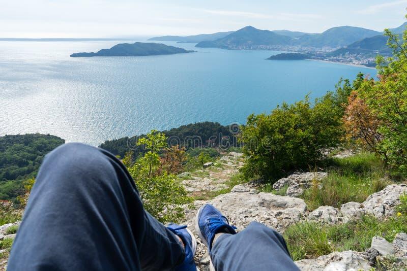 Primo fare un giro turistico di prospettiva della persona della costa adriatica in Budua, Montenegro Gambe con le scarpe da tenni fotografia stock libera da diritti