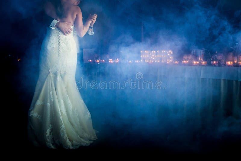 In primo luogo balli la sposa e lo sposo nel fumo fotografia stock libera da diritti