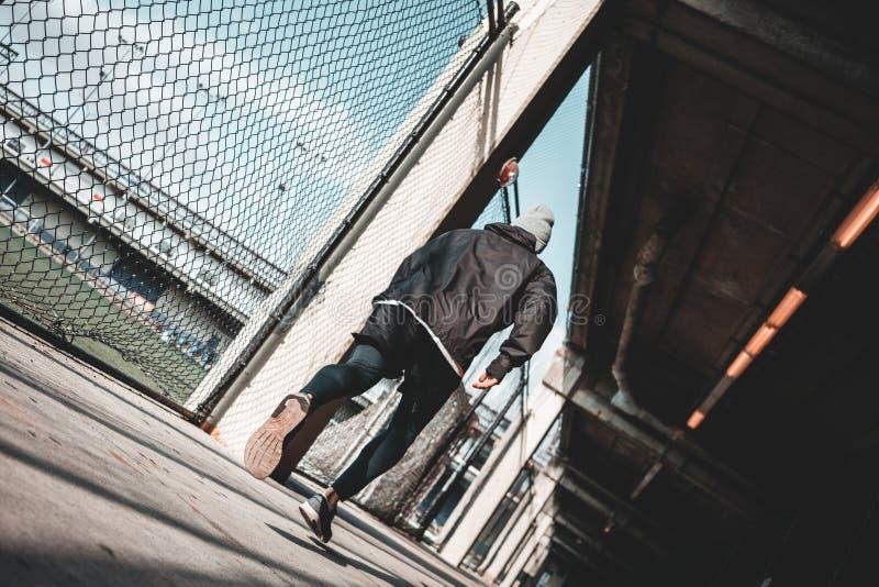 Primo mattino corrente veloce dello sportivo nel giorno soleggiato con la vista urbana fotografia stock