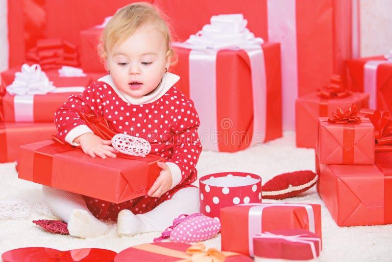 Primo natale del bambino una volta nell'evento di vita Piccolo gioco della neonata vicino al mucchio dei contenitori di regalo Re fotografia stock