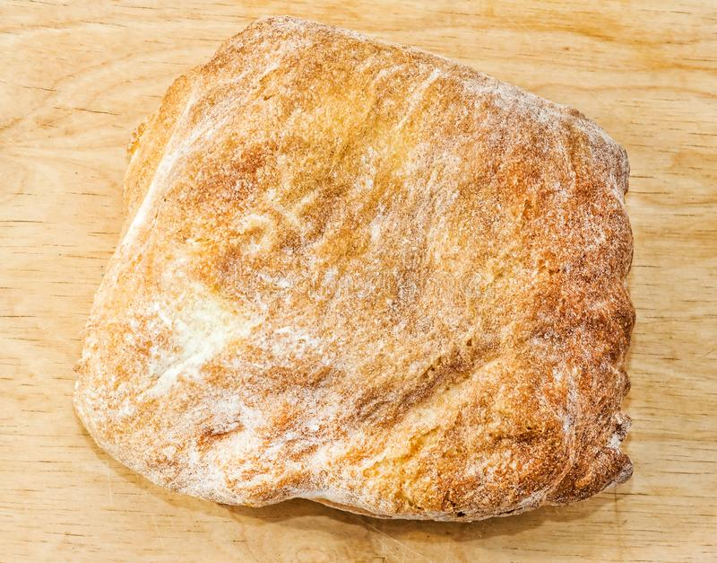 Primo piano al forno fresco del pane italiano di ciabatta sul bordo di legno Vista superiore fotografie stock libere da diritti