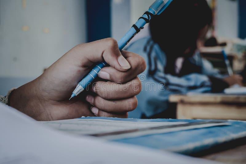 Primo piano alla mano della penna di tenuta dello studente ed all'esame di presa nel classr fotografia stock