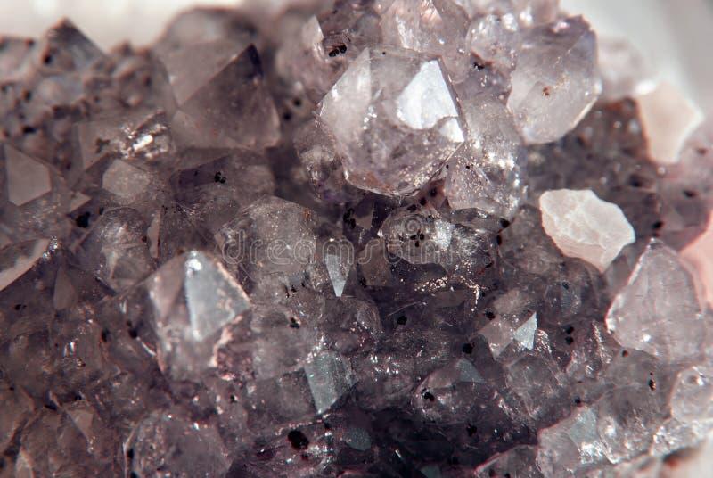 Primo piano ametista della pietra preziosa come parte del geode del mazzo riempita di cristalli di quarzo della roccia fotografia stock libera da diritti