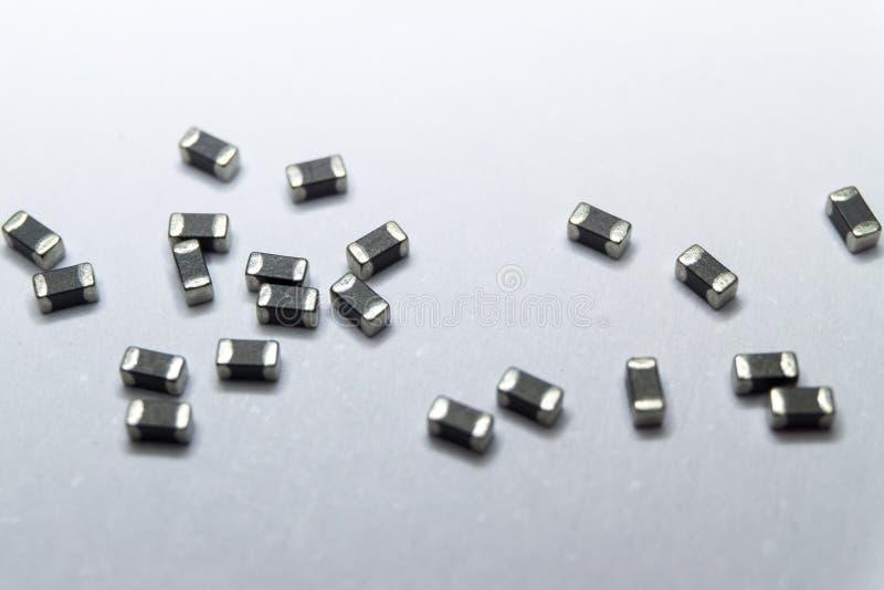 Primo piano astratto di grigio sparso 0402 componenti di elettronica di potenza della perla di ferrite del chip del supporto dell fotografie stock