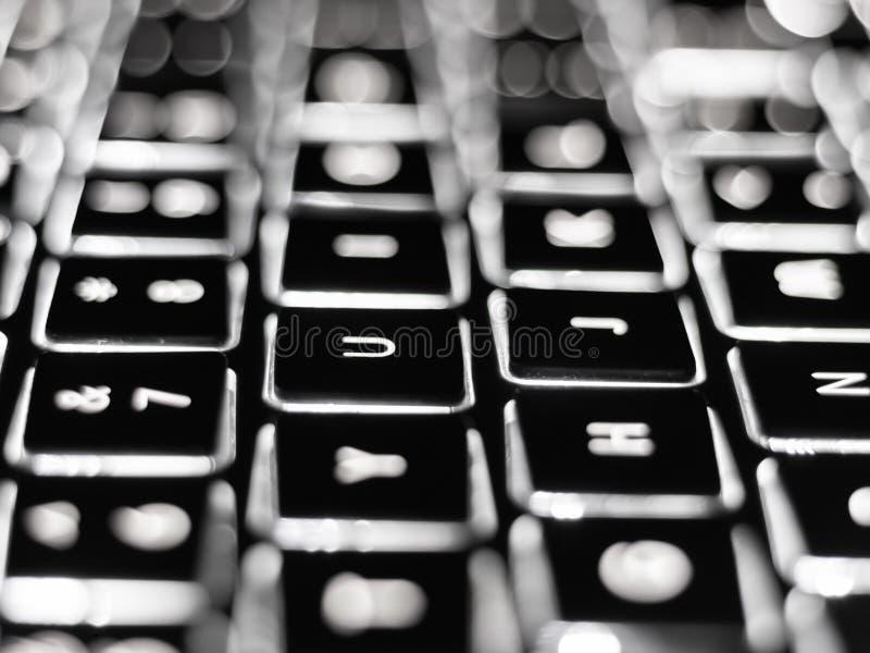 Primo piano in bianco e nero sulle chiavi illuminate della tastiera di computer fotografia stock libera da diritti