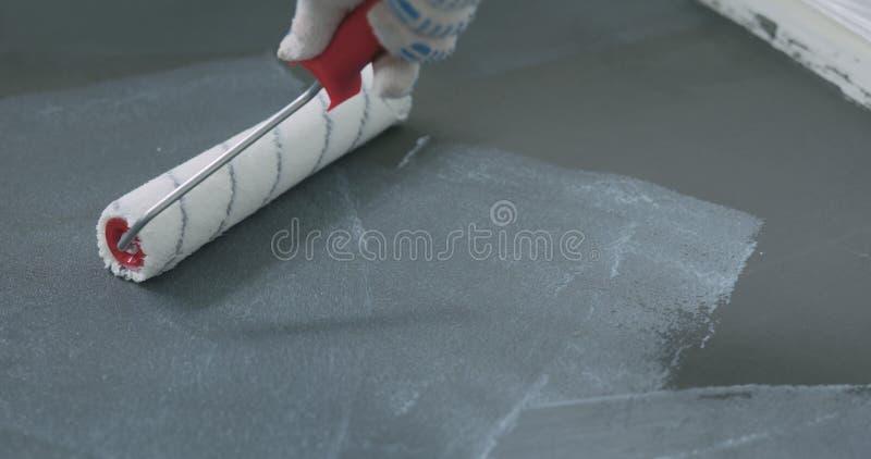Primo piano che applica rivestimento protettivo sul pavimento di calcestruzzo fotografia stock libera da diritti