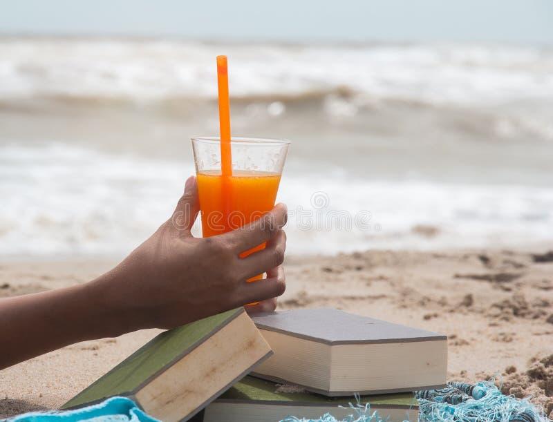 Primo piano che il vetro di succo d'arancia stava tenendo dalla mano di signora, accanto al libro impilato, sulla spiaggia fotografia stock