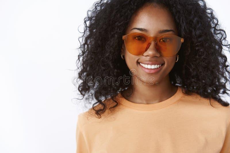 Primo piano che incanta giovane femmina dalla carnagione scura alla moda alla moda che porta la maglietta arancio degli occhiali  fotografia stock libera da diritti